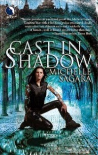 Cover art for Cast in Shadow, featuring a pale, leather-clad woman with dark hair crouched in front of a blue-toned, arched architectural feature. The woman has dark, non-arabic characters marked on her arms.