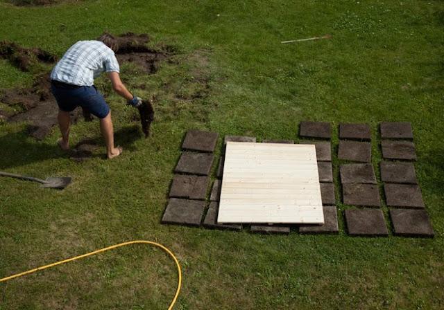 En man gräver upp plattor som legat under gräs.
