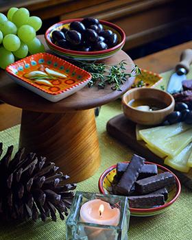 Uma tábua com queijos, frios, frutas e chocolates