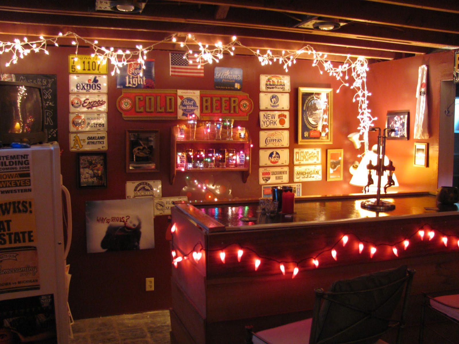 Shot of the basement bar and back wall in full splendor.  Christmas lights glow and signs cover the walls