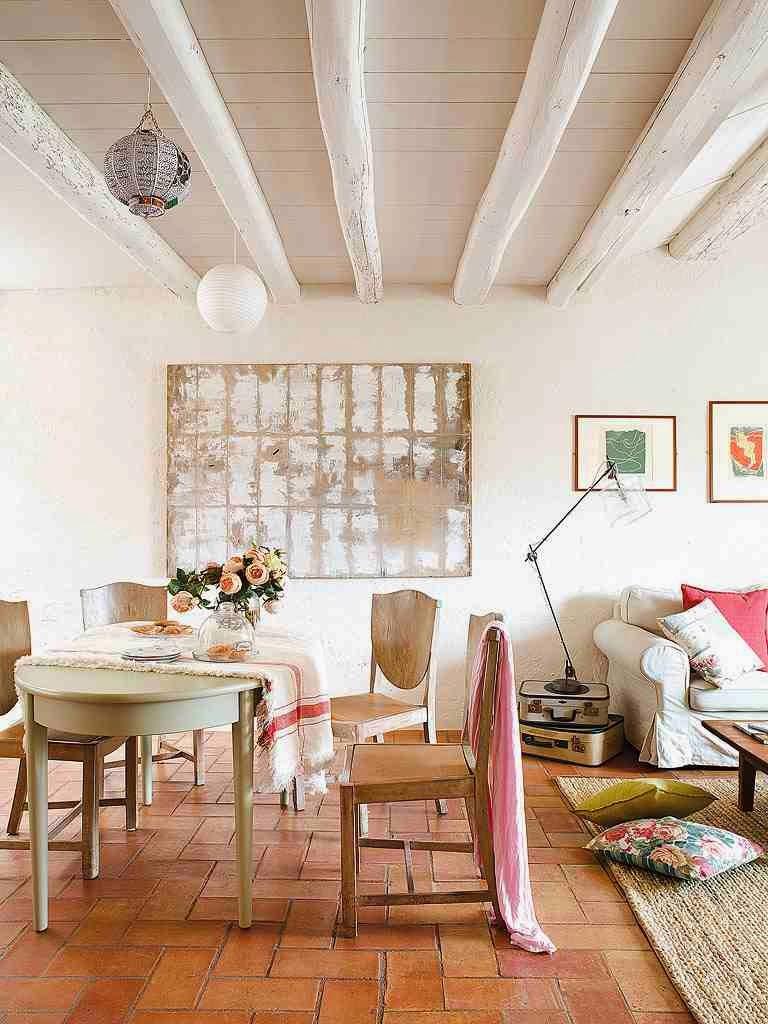 Eklektyczne wnętrze salonu z jadalnią, drewniany stół, drewniane krzesła, dekoracyjne stare walizki na podłodze