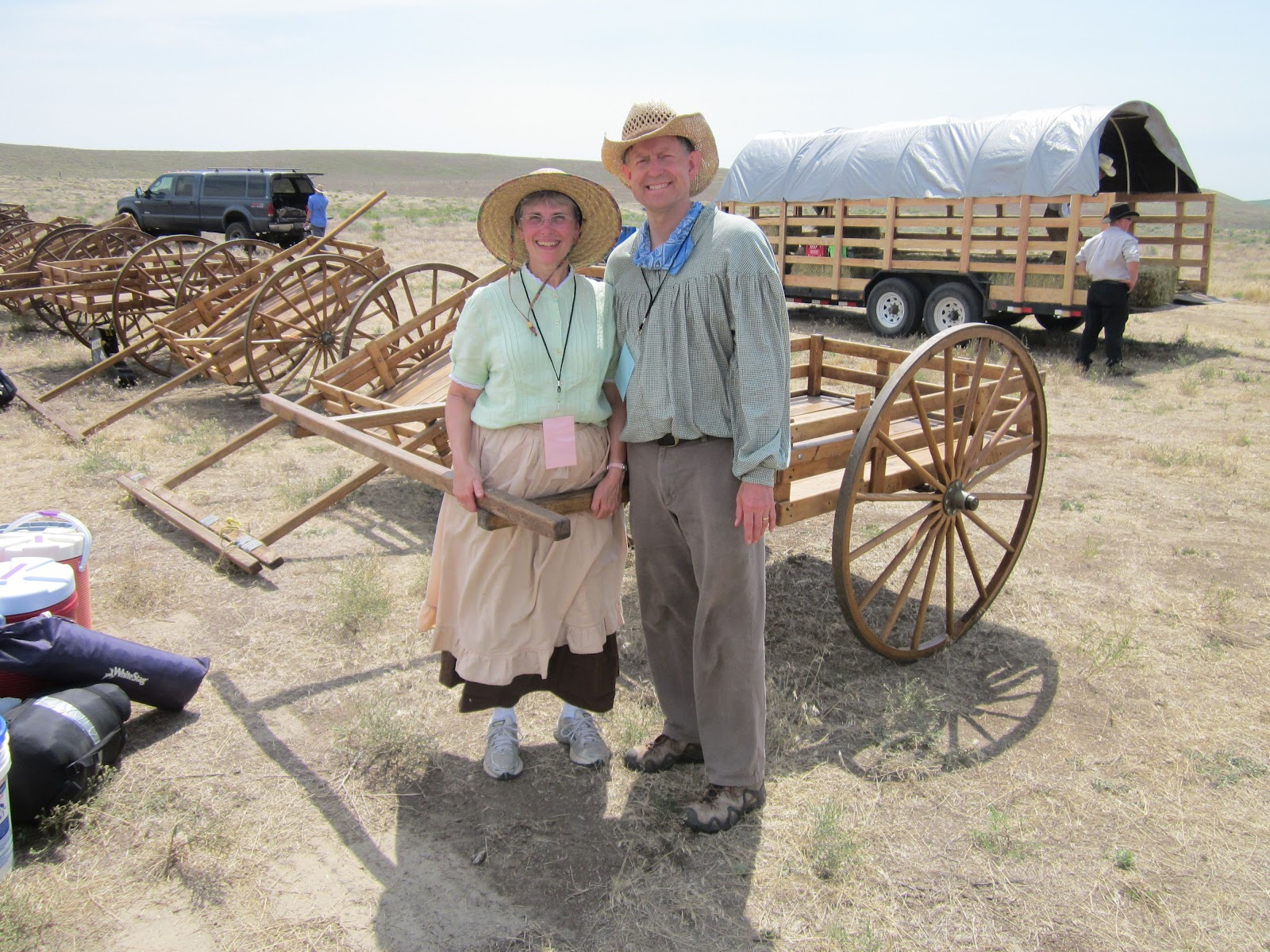 at the start of the week our pioneer clothes are still fresh and clean we are standing near the handcarts that the kids will be pulling through the dust