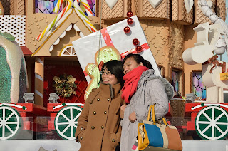 Two women pose in front of the Christmas display at Oriental Plaza in Beijing