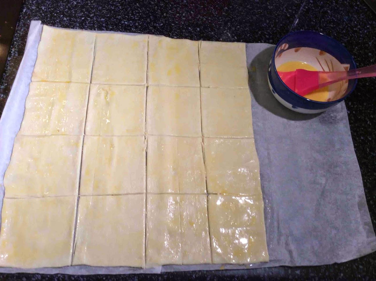Masa de hojaldre cortada y pintada con yema de huevo