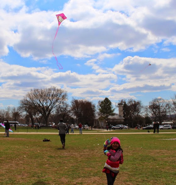 Happy child running trying to fly a kite at the National Mall
