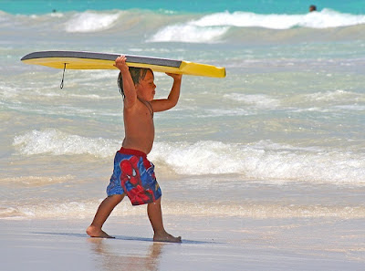 child with boogie board at beach