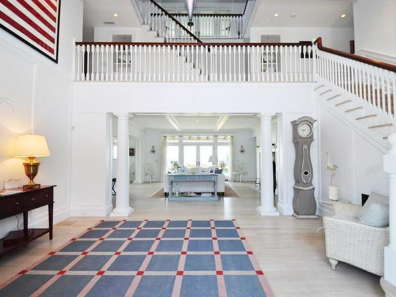 Nautical theme foyer with white staircase, light wood floor, blue, white and red rug, white wicker chairs and a view of the living room