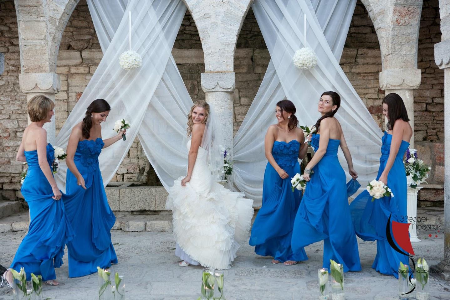 булката и шаферките с тъмно сини шаферски рокли се забавляват на фотосесията в Балчик