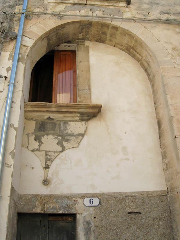 In un vicolo di Ragusa Ibla, sovrapposizioni su una facciata