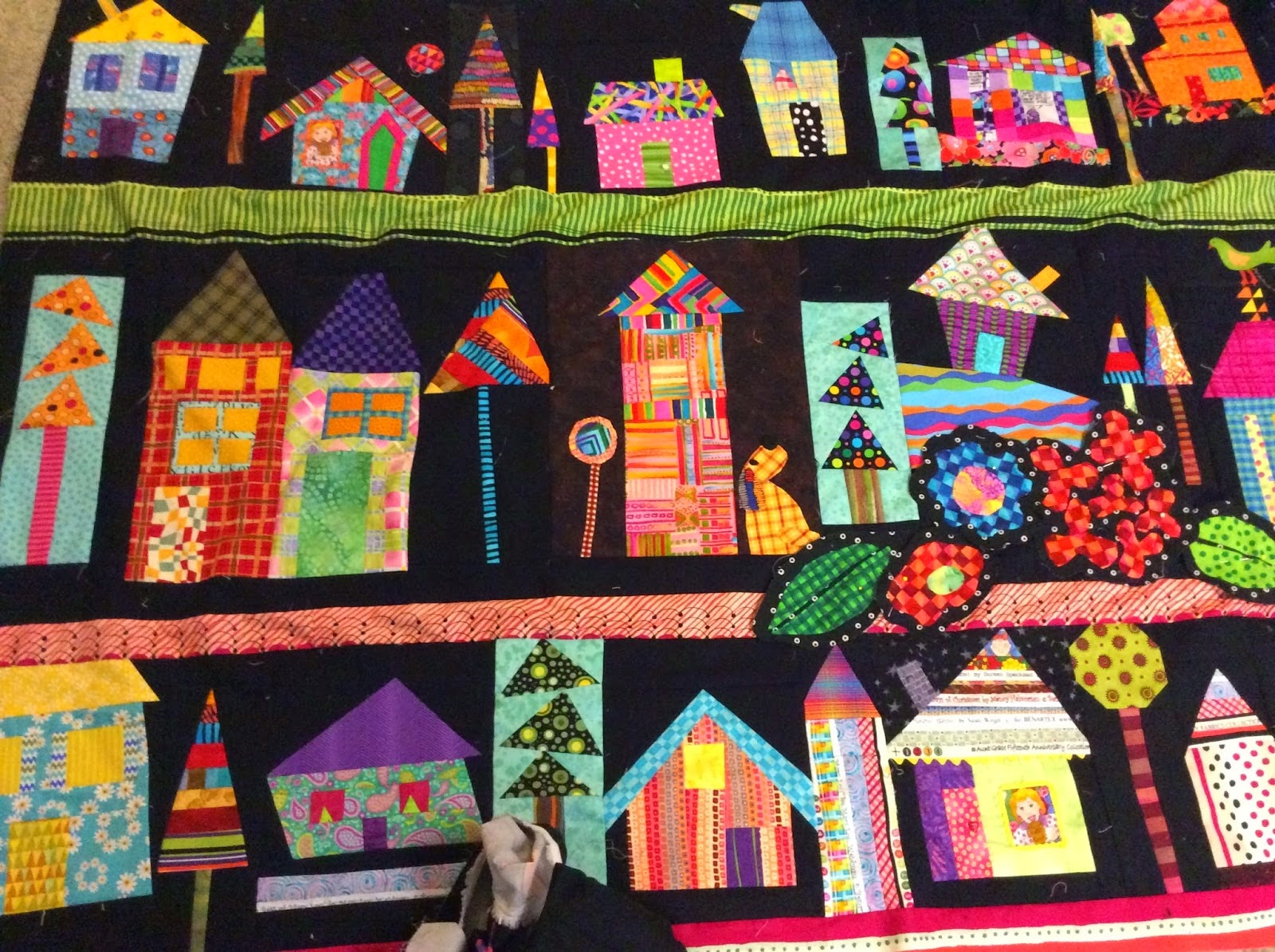 House quilt is done and quilted with fun details and whimsical things to smile at