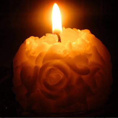Cream coloured spherical rose patterned candle with a glowing cosy flame.