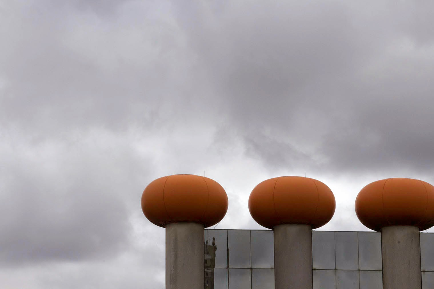 three orange balls and a grey sky