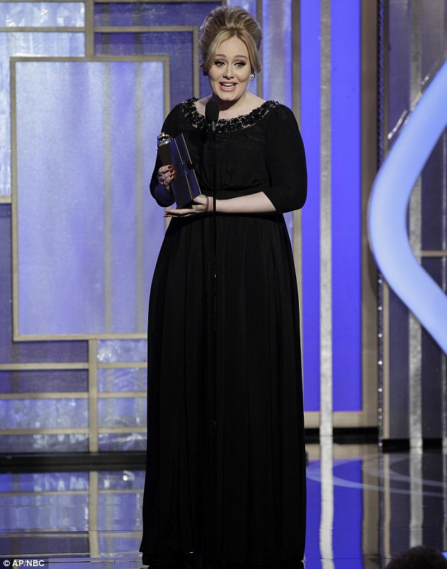 Adele wearing a Black Burberry gown accepted her award on stage