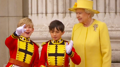 Pageboys and Queen Elizabeth looking at planes from the balcony. YouTube 2011.