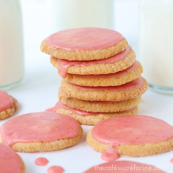 Photo of a stack of Strawberry Glazed Butter Thins with jars of milk in the background and cookies in the foreground.