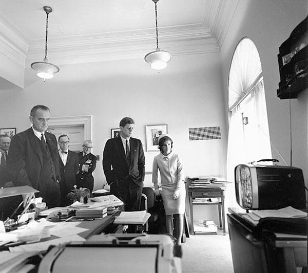 Grace Intemporelle by Natalia: Con John y otros viendo el vuelo del atronauta Shepard en televisión en 1961. Aunque no se indica quién diseñó lo que lleva, vemos su clásico traje sastre modernista y su clásico sombrero pillbox.