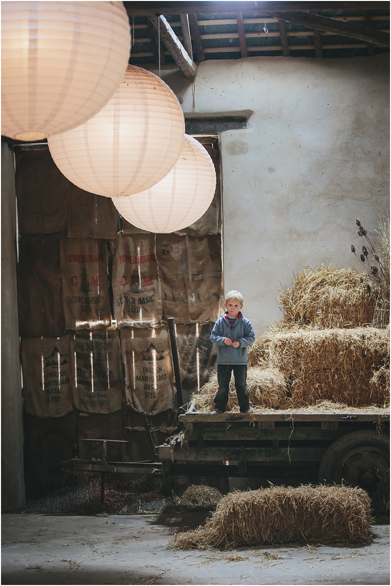 A young boy playing in a barn
