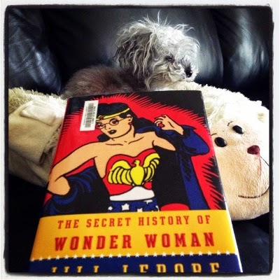 Murchie lays on a pillow shaped like a sheep. Before him, occupying most of the foreground, is a hardcover copy of The Secret History of Wonderwoman. Its cover features a vintage drawing of Wonder Woman removing a blue coat to reveal the red bustier and blue knickers beneath it.