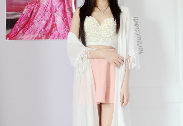 A cute, boho, ulzzang-style summer OOTD, with a pastel pink skater skirt, fringed longline kimono, and beaded bustier top.