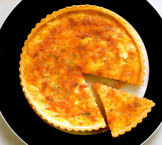 Classic quiche lorraine of a savoury egg custard containing cheese, shallots and bacon in a flaky pastry shell.