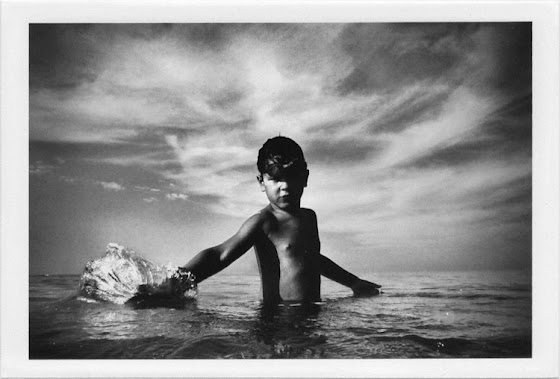 dirty photos - et - a black and white photo of boy playing with water inside the sea