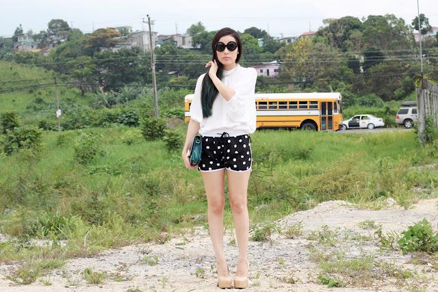 Lentes circulares, camisa de botones, pantaloncillos de lunares y zapatos plataforma