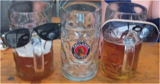 beer glasses dressed with sunglasses using handle as nose
