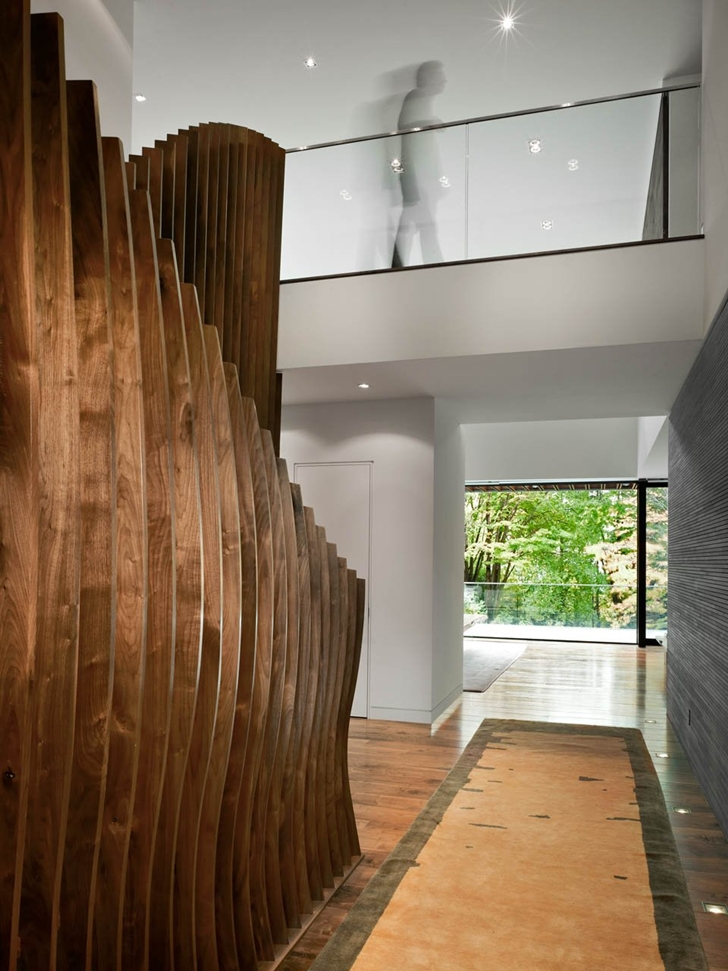 Wooden stairs and hallway in Modern mansion by Belzberg Architects Group
