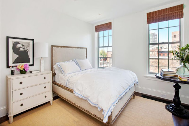 cozy guest room with upholstered headboard, white chest of drawers, two windows and a black desk