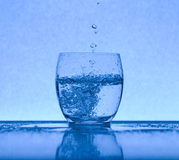 Un bicchiere con metà acqua il blu predomina sulla fotografia ma ci sono anche bollicine d'acqua