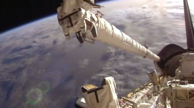 Canadarm extending from the payload bay to inspect the underside of the shuttle. NASA 2011.