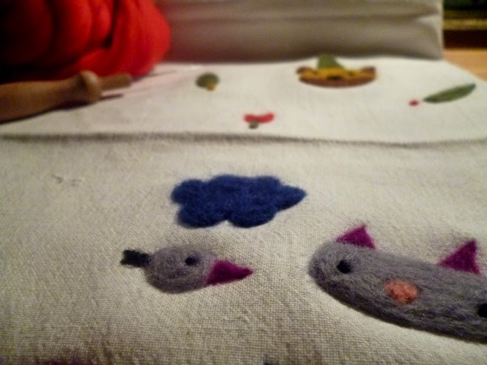 Purple and grey bird and cat and blue cloud, needle-felted on white fabric