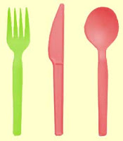 Green fork next to red spoon and knife