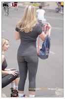 Hermosa rubia patinando en la calle con spandex ajustado , se le marca