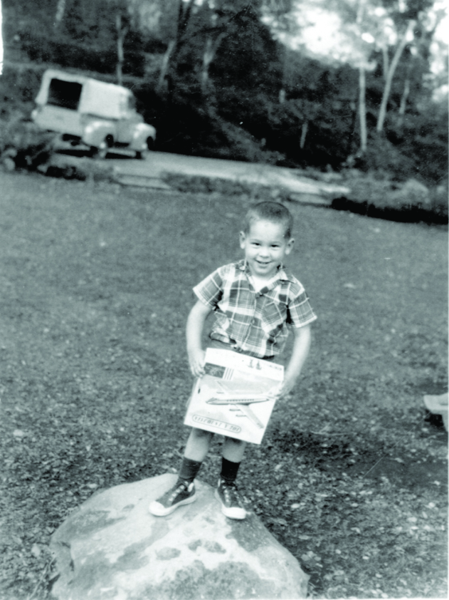 Paul at four years old holding a model airplane.  His future trademark Ford F1 Pickup is behind him.
