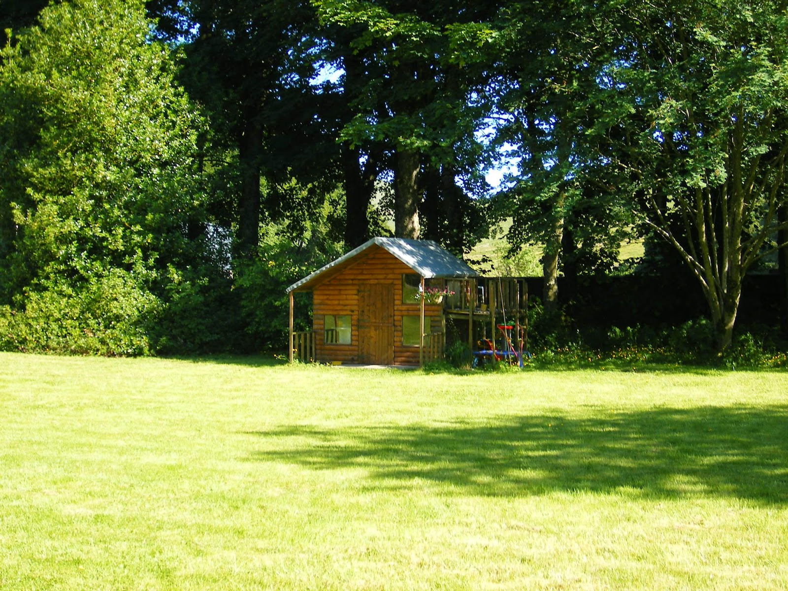 country garden with trees, lawn and playhouse in summer