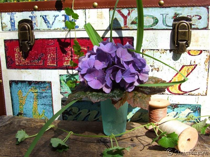 Blumendeko mit blauen Hortensien