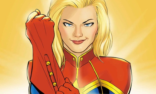A blonde white woman, Captain Marvel, wears a determined expression on her face as she pulls on a red gauntlet-style glove.