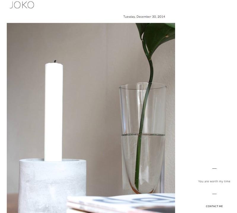 valkoinen kynttilä harmaassa betonijalassa