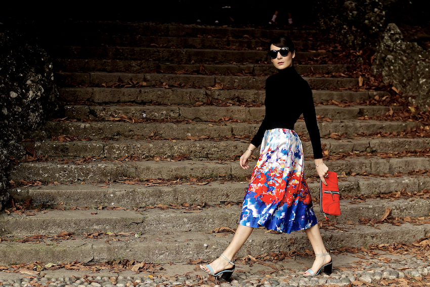 irene buffa in milan wearing a print colorful flare midi skirt , sandals and a red clutch
