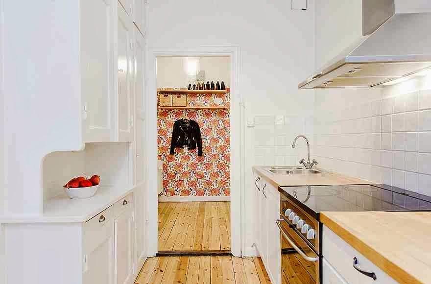 Widok z białej kuchni na przedpokój i kolorową tapetę
