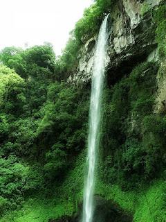Foto lateral da Cascata da Gruta Nossa Senhora de Lourdes, em Galópolis, Caxias do Sul. Vista da queda d´água e da mata nativa.