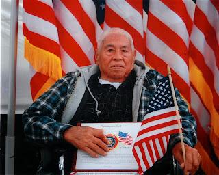 Félix García, orgulloso ciudadano estadounidense, con la copia del Juramento de Naturalización y la bandera de los Estados Unidos en mano.