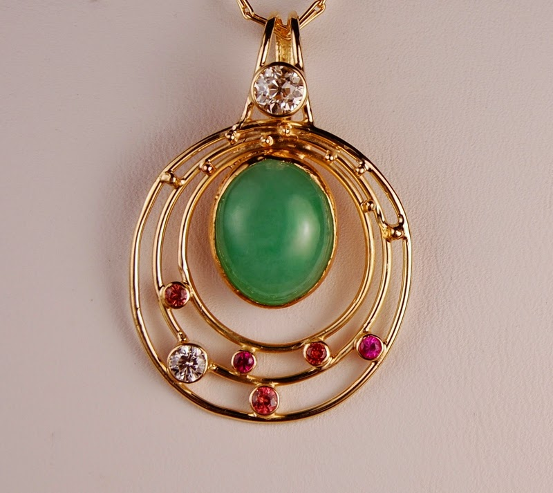 green stone pendant with concentric rings around it and white and pink/orange stones