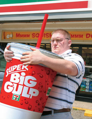 an obese man carrying a Super Big Gulp soda drink cup from The Onion