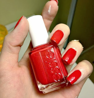 Holding a bottle of Essies Lollipop nail polish, a bright red.