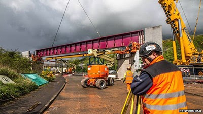 A Network Rail operative guides a bridge into place