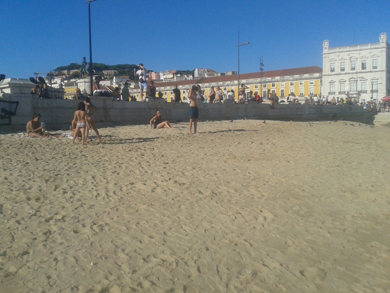 Banhista a apanhar sol na praia de Lisboa