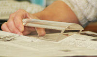 An individual uses assistive technology, a magnifying reading device