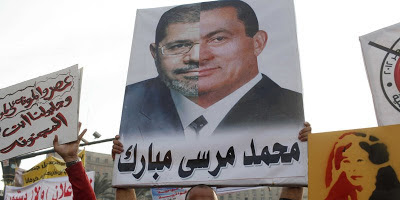 Protester with poster comparing Morsi and Mubarak